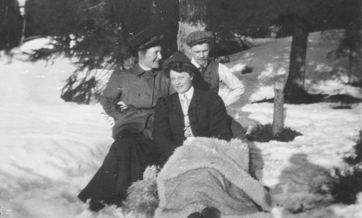 To kvinner og en mann sitter i snøen under en gran. Påsken i Nittedal.