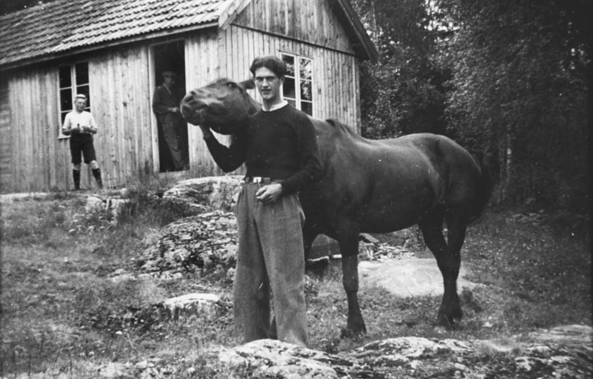 Mann og hest på gårdstun (Kåre Høybråten f. 1911).