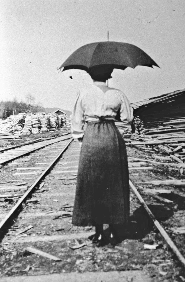 Fru Boeck (bakfra med paraply) ute i skinnegangen på sagbruket