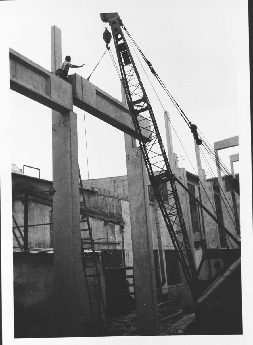 Ombyggingsarbeider ved Strømmens Verksted, byggningselementer, heisekran, arbeidere.