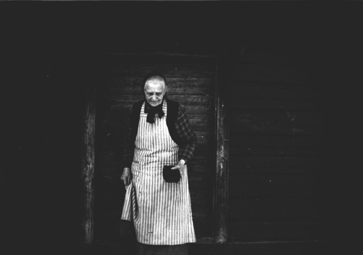 Eldre kvinne på stabburstrapp.