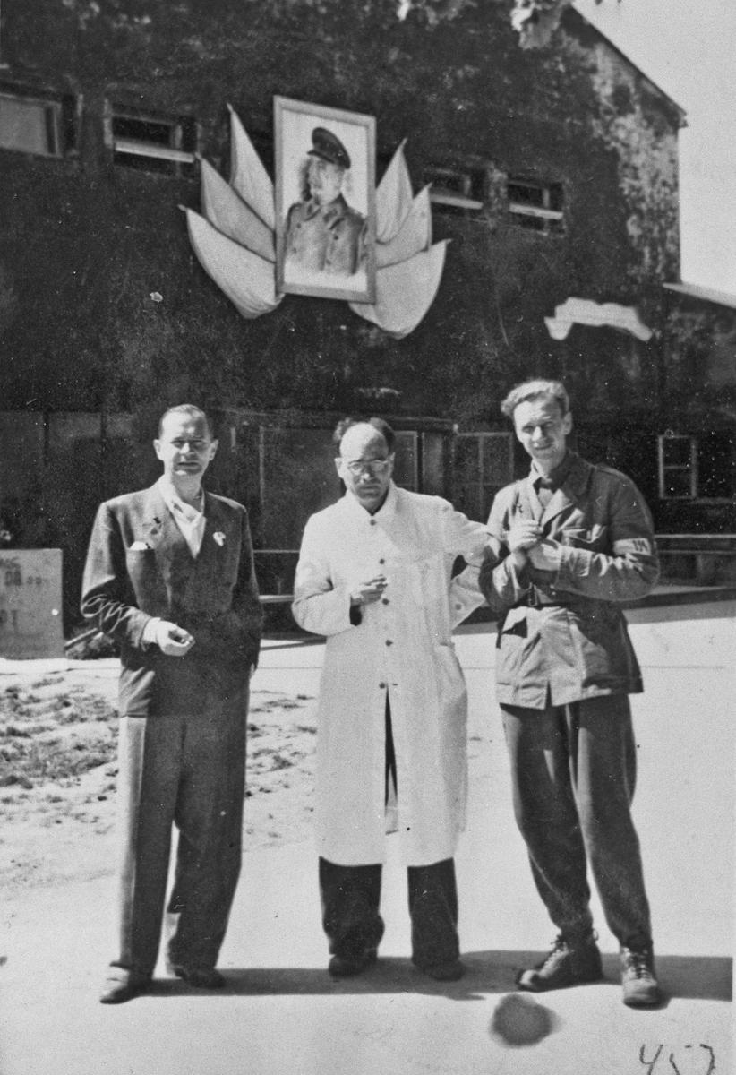 En fra Hjemmestyrkene og en lege. Bilde av Stalin i bakgrunnen.