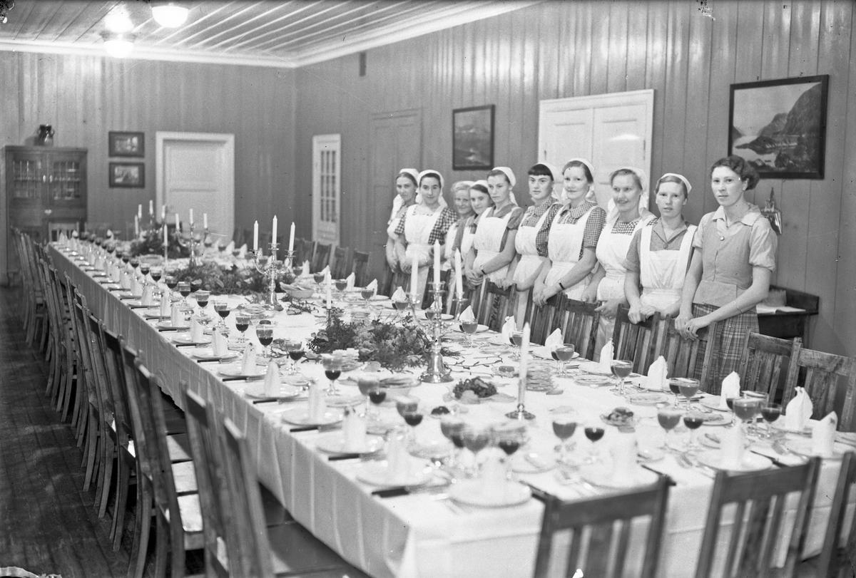 Kvinner ved bord dekket til selskap. Nr. 6 fra v.: Tordis Holt (g. Håkens). På Akershus Fylkes Husmorskole i Eidsvoll i 1941 eller 1942.