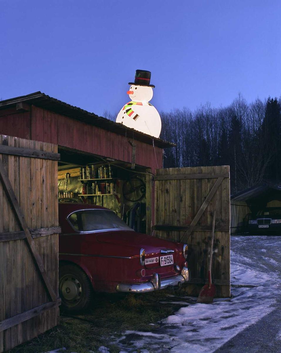 Julebelysning.  Fantastisk julebelysning. Lysende snømann sitter opp på garasje ved enebolig.