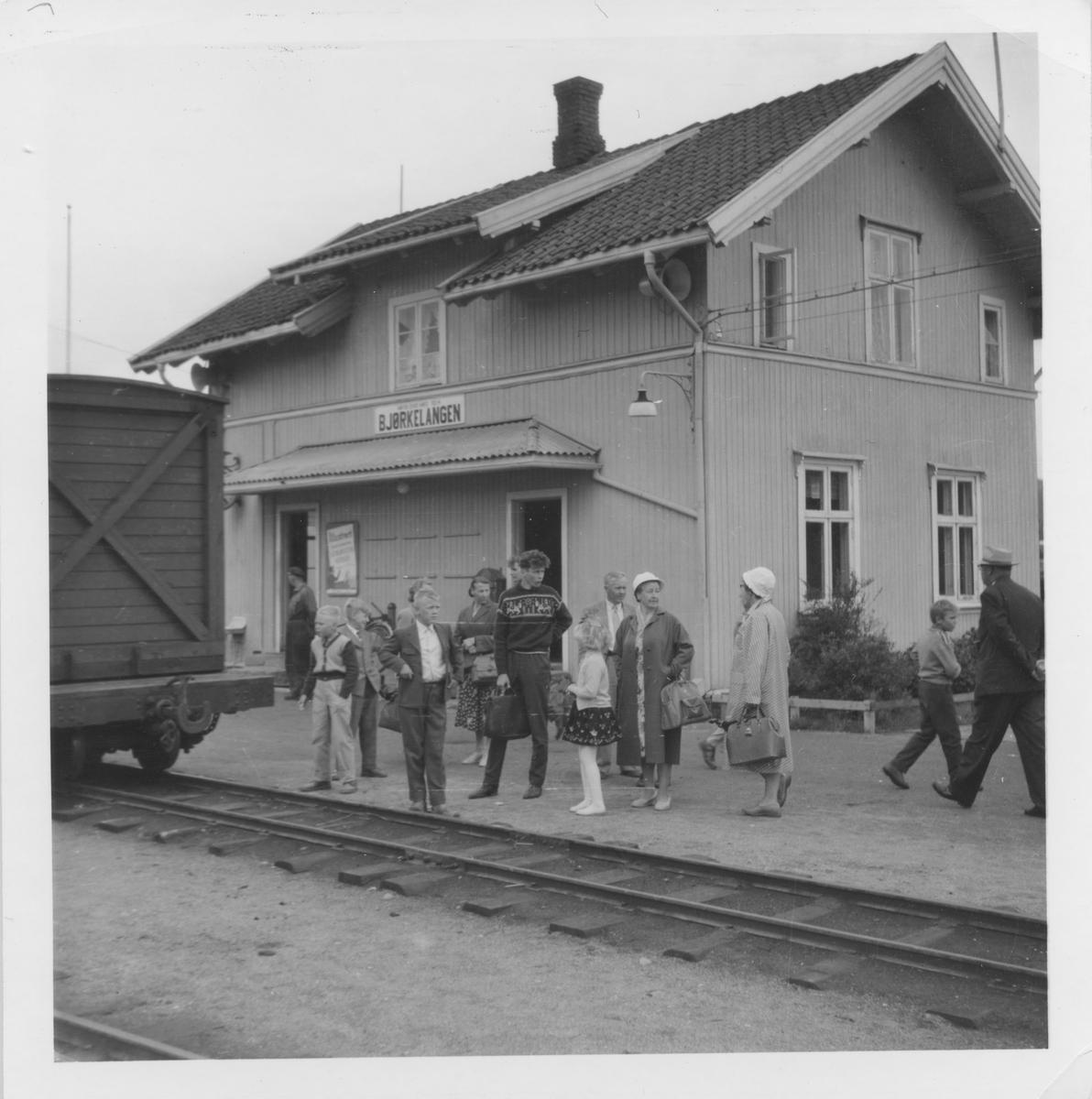 Reisende venter på plattformen mens lokomotivet fyller vann.