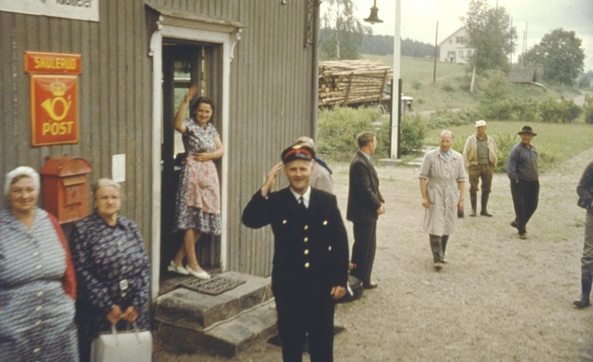 Stasjonsbetjent og lokalbefolkning vinker farvel til siste ordinære tog fra Skulerud.
