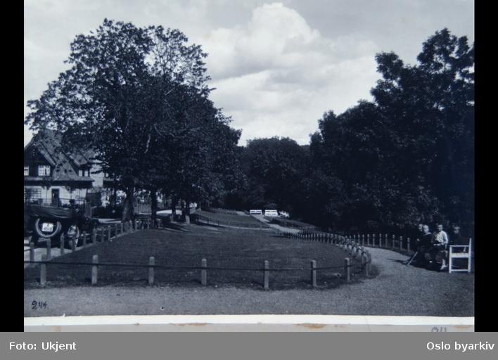 """Parkområde på Ullevål Hageby, muligens langs Ullevålsalleen, med benker og grusganger. Åpen bil. Sannsynligvis fra 1920-tallet. Albumtittel: """"Fotografier over Kristiania kommunes boligbebyggelse II""""."""