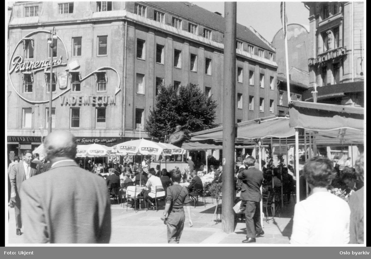 """Uteservering (""""Dasslokket"""") under parasoller på Stortings plass. Christian Krohg-statuen. Brambanigården med veggreklame for """"Barnengens Vademecum"""". Centralgården til høyre. Arbeidergata."""