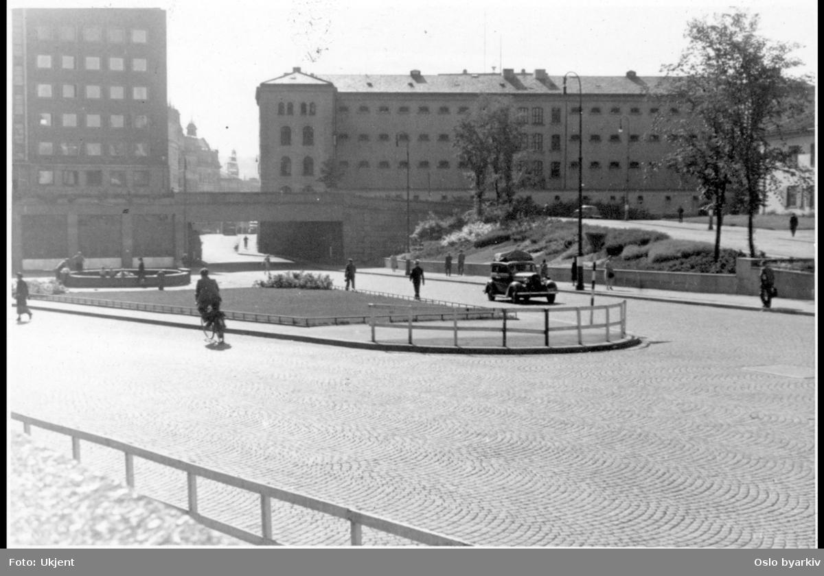 Arne Garborgs plass brosteinbelagt med grøntanlegg og fontene. Hospitalsgata i fra Akersgata til Møllergata nedsenket under Grubbegata. Hovedbrannstasjonen med garasjeanlegget. Fengselsbygningen til Møllergata 19 (revet 1981) mot Grubbegata til høyre. Til høyre ses Militærhospitalets hovedbygning. I forgrunnen Henrik Ibsens gate (nå Hammersborggata).