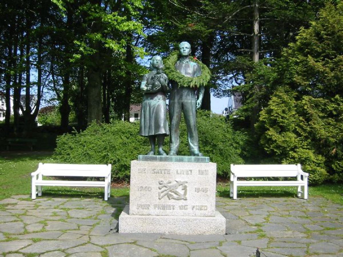 Skulptur i bronse av mann kvinne og barn i full størrelse 2 m høye figurer. Under en sokkel i granitt, med emblemetr Tro håp og Kjærlighet anker og kors, . H 0,90, B 1,40, D 0,90.