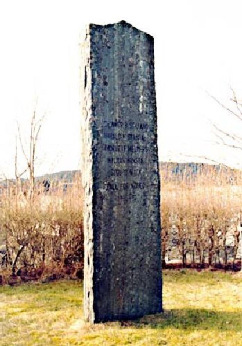 Vel 2 m høg naturstein med med innhugget innskrift.