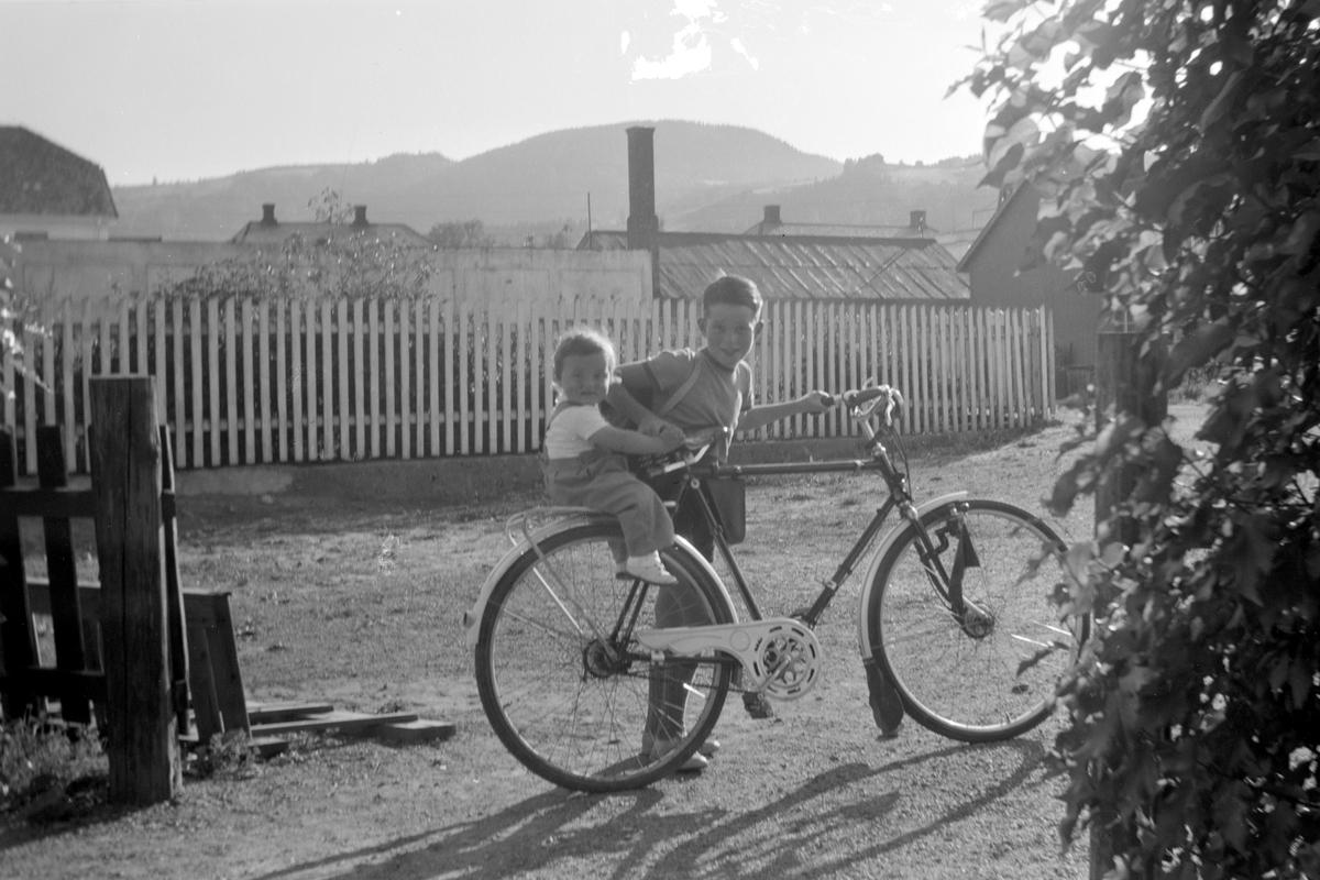 Mordal i Nygata 21 i Brumunddal.  Svein-Erik Mordal f. 1941 med Vilde Kari Mordal f. 1952 på bagasjebrettet. Sykkel.