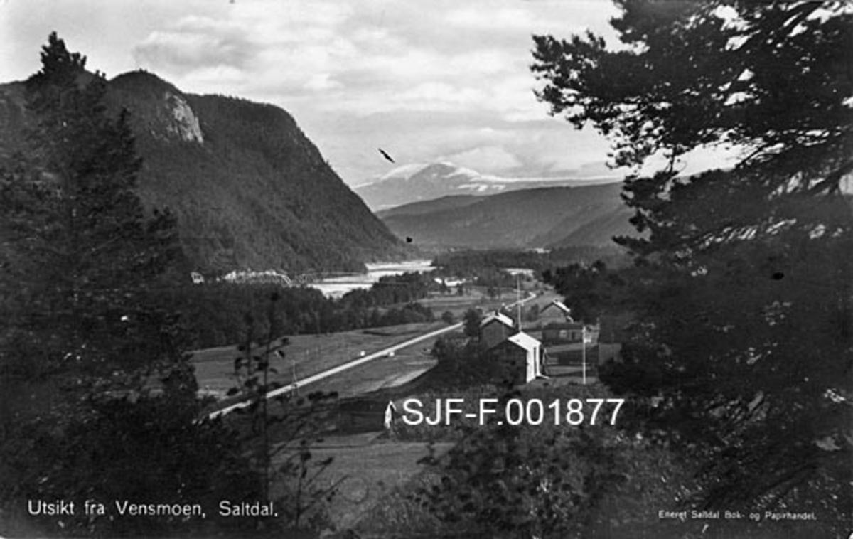 Landskapsbilde fra Vensmoen i Saltdal i Nordland.  Fotografiet later til å være tatt fra en bakkekam, mellom furu- og bjørketrær, mot ei elveslette med gardsbruk omgitt av jorder.  Over sletta og jordene går det en veg.  Vegen går for øvrig noenlunde parallelt med et vassdrag, antakelig Saltdalselva.  På motsatt side går et forholdsvis bratt, men stort sett skogkledd fjellmassiv ned mot elva.