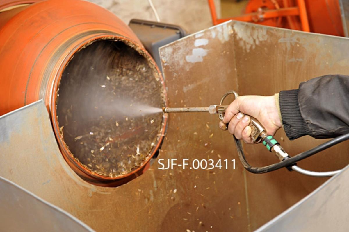 """Det sprøytes finforstøvet vann inn i en betongblander, som på forhånd var fylt med granfrøhams, altså nyklenget frø som fortsatt hadde """"vingene"""" som i naturen skulle føre frøet bort fra mortreet intakt.  Det var på ingen måte hensiktsmessig å la disse vingene følge med til skogplanteskolene eller andre frøkjøpere.  Derfor ble frøet avvinget, i dette tilfellet ved en prosess som kaltes for våtavvinging.  Etter at frøhamsen var fuktet fikk maskinen gå noen minutter, slik at massen ble godt eltet, før det ble tilført luft for å tørke frø og frøvinger igjen.  Blåselufta, som kommer fra et par støvsugerliknende innretninger på en hjell over de tre betongblanderne som ble brukt, føres gjennom den smale, grå slangen som her henger over armen til operatøren og karet foran betongblanderen.  Etter hvert som innholdet tørker, får rotasjonen og luftstrømmen de lette frøvingene til å løftes opp og flagre ut.  De samles opp i digre blikkbeholdere foran betongblanderne.  Den større, grå slangen lengst til venstre i bildeflata, er et avsug.   Da dette fotografiet ble tatt hadde Skogfrøverket også fått en spesialmaskin for frøavvinging.  Ved denne anledningen var den imidlertid full av furukongler, og frøverksmedarbeideren som hadde hovedansvar for den praktiske frøproduksjonen fant det like greit å bruke betongblanderne."""
