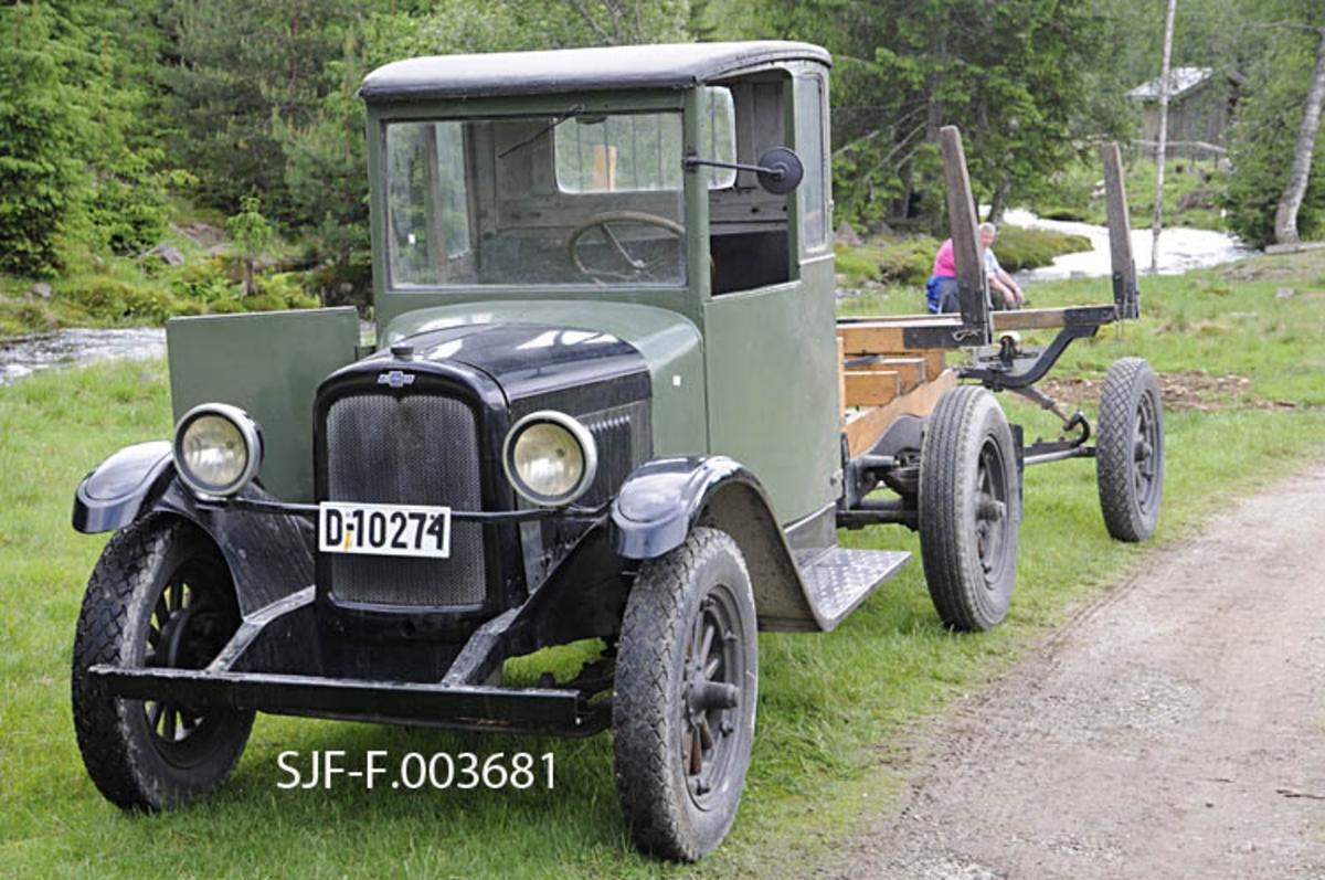 Chevrolet-lastebil, utrustet for tømmertransport.  Bilen, som antakelig er fra 1930-tallet, har svart motorkasse og grågrønt førerhus.  Ramma som bar tømmerstokkene på den bakre delen av chassiet og en bakenforliggende tohjuls tilhenger, var utført i tre.  Denne veteranbilen tilhører i dag en kar fra Odalen.  Her er den fotografert ved Gammelsaga i Stange almenning, der den ble brukt i forbindelse med gjenåpningen av stedets lokomobilsag i forbindelse med bruksrettsbefaring i Stange og Romedal allmenninger 10. juni 2011.