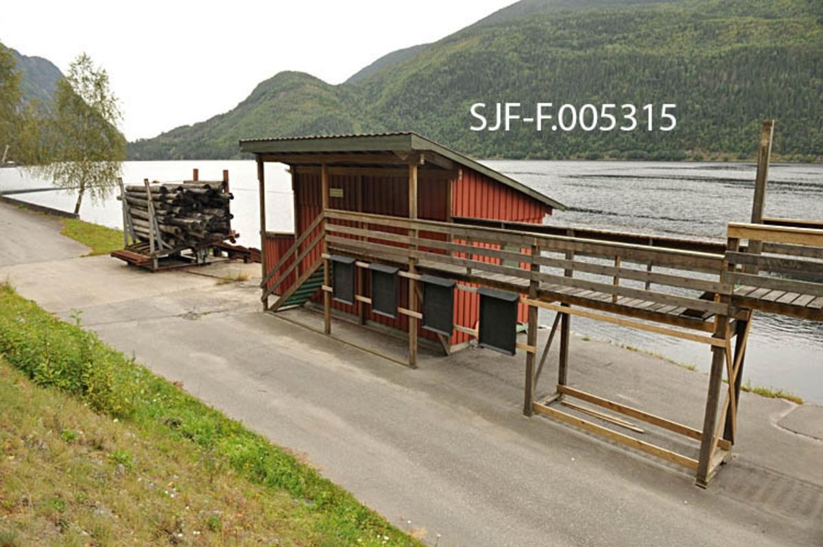 Utislagsplass med tømmermålingsfasiliteter ved Dalen i Tokke i Telemark.  Anlegget ligger like øst for tettstedet, ved den såkalte Lasteinsvingen.  Her er det bygd en veg langs stranda mot Bandak.  Mellom denne vegen og skråningen ned mot vatnet er det plassert ei inspeksjonsrampe for tømmermålerne, som måtte litt opp fra bakken for å kunne måle høyden og bredden på tømmerlassene og danne seg et brukbart inntrykk av fastmasseprosenten.  Bakenfor ser vi den rødmalte brakka med pulttak der målerne hadde kontoret sitt.  Bak den igjen skimter vi ei «vogge», et stativ som tømmerlassene ble veltet over i fra bilene.  Her ble tømmeret buntet («klubbet»).  Så kunne stengene på sida mot sjøen løsnes.  Deretter ble den bakre (indre) delen av vogga hevet ved hjelp av hydrauliske heisemekanismer, slik at tømmerbuntene («klubbene») skled via kraftige stålbjelker på den bratte strandskråningen og ned i vatnet.  Bildet er tatt fra vest mot øst.   På Bandak, like utenfor utislagsstedet, ble tømmerbuntene bundet sammen i slep, som ble trukket over Vestvannene (Bandak, Kviteseidvatn og Flåvatn) med slepebåt.  Fram til cirka 1980 ble tømmeret fløtet videre ned gjennom sluseanleggene Bandak-Norsjøkanelen, over Norsjø, og via Løveid sluser til Skien.  Fra da og fram til tidlig på 2000-tallet ble tømmeret fra Vest-Telemark tatt opp ved Kåsa, like ovenfor det øverste sluseanlegget (Hogga), og kjørt videre med lastebiler.  De første forsøkene med utislag fra brygge ved Dalen ble gjort like etter 2. verdenskrig.  Etter at den nye kraftstasjonen ved Dalen ble satt i drift i 1961 ble slik levering det normale for tømmer fra Tokkevassdragets nedslagsfelt.  Lassmåling av tømmer («FMB-måling») ble innført i Norge – antakelig også i Vest-Telemark – tidlig i 1970-åra.  Denne målemetoden ble i hovedsak brukt på slipvirke, altså lavkvalitetsvirke som skulle til treforedlingsindustrien.