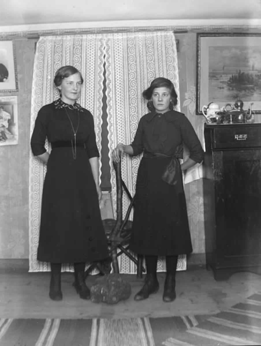 Två unga finklädda flickor framför en spetsgardin. Interiör från rum med trasmattor på golvet. Se även bild HB 513