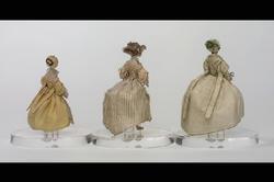 Inventering Sesam 1996-1999: a) Docka i gul klänning  H  7,4 cm b) Docka i vit klänning med grönvita band  H  8,5 cm c) Docka i vit klänning med svarta ränder  H  9 cm 3 st dockor i 1600-talsdräkter, huvuden klädda med satinvävt siden, kroppar, armar, ben, strumpor, skor och händer med separata fingrar, av metalltråd, klädd med virad silkestråd. Målade och broderade ansiktsdrag, frisyrer av äkta hår. Bindmössor och kragar hålls fast med knappnålar. a) Iklädd klänning med snörning i ryggen och breda band hängande ned från axelsömmmen, av gult siden, dito bindmössa och underkjol, vit spetskrage, underämar och förkläde av vit silkesväv, förklädet med kantspets. Vit underkjol. Röda strumpor. Flätad krans av brunt hår bak på bindmössan. Saknar en hand. b) Iklädd klänning med snörning i ryggen och breda band hängande ned från axelsömmen, av vitt siden, garnerat med smala band i vitt och grönt, dito bindmössa och underkjol. Lintyg. Rester av krage och förkläde. Svarta skor med rosetter, röda strumpor och strumpeband (band såsom klänningen). Svart halsband av tråd (pärla saknas, jfr äldre katalogkort). Flätad krans av brunt hår bak på bindmössan. Kjolen troligen alltför uppuffad vid tidigare konservering. c) Iklädd klänning (över- och underklänning) med snörning i ryggen, av vitt siden med smala svarta ränder, garnerad med vita rosetter, krage av knypplad spets. Lintyg. Halsband och örhängen av vita pärlor. Röda strumpor och vita skor. Frisyr med flätad krans av brunt hår, skruvlockar vid sidorna och vita rosetter. Saknar båda händerna. Klänningen starkt nedbruten. Kjolen troligen alltför uppuffad vid tidgare konservering. Enl huvudliggaren har a) tillhört fröken Siri Oxenstierna. G. ss porträtt, inv nr 2.186. /Anna Womack nov 1997