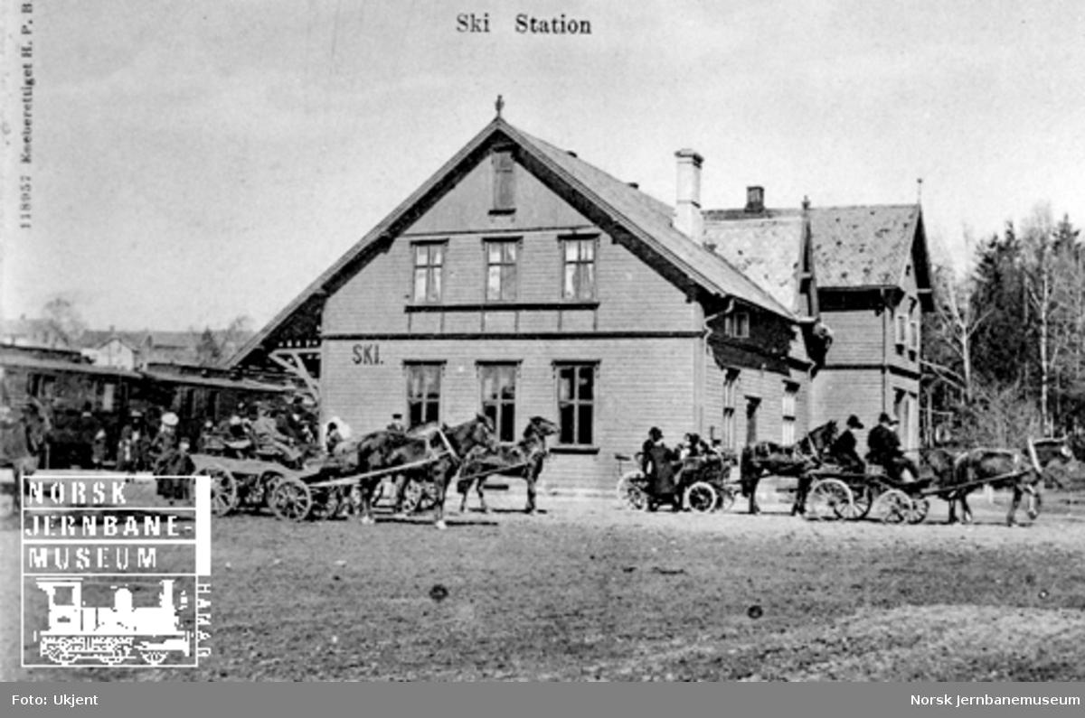 Ski stasjon med et persontog i spor 1 og mange hester med vogner foran bygningen