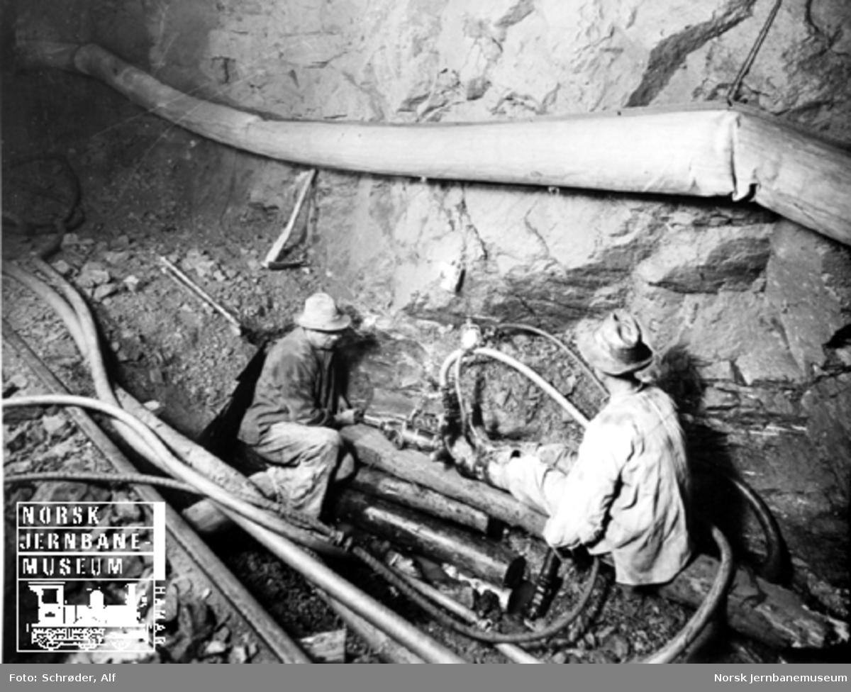 Medjå tunnel : to anleggsarbeidere borer en drensgrøft
