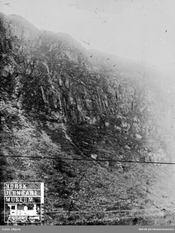 Fra Flekkefjordbanen før anlegget, parti fra Drangsdalen med fjellrekken fra Lyngodden til Øiktofjell; jernbanelinjen er inntegnet med svart tusj