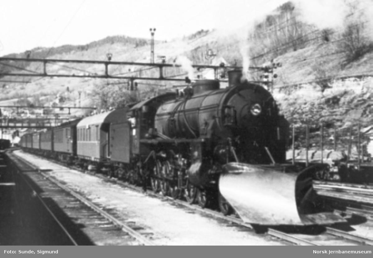 Damplokomotiv type 31b nr. 429 med stor frontplog foran et persontog