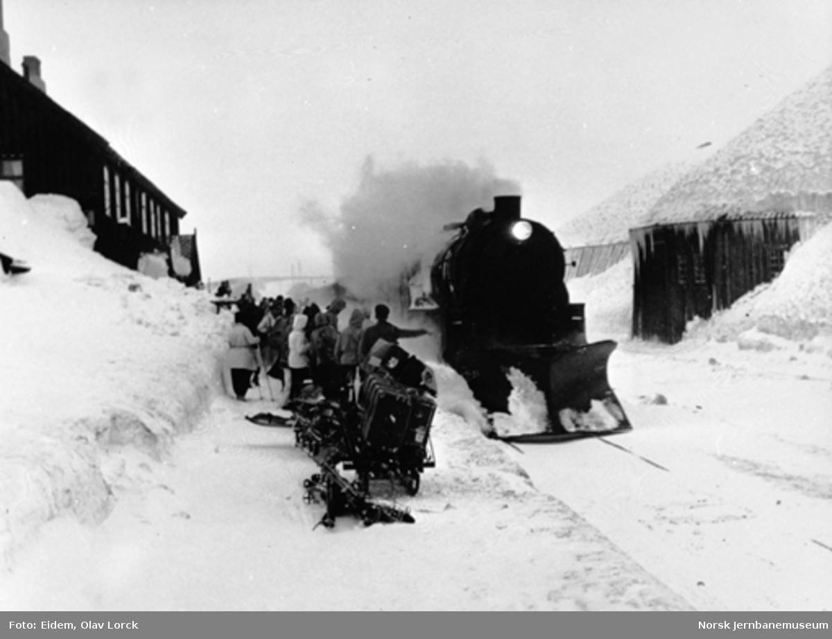 Damplokomotiv ankommer Finse stasjon med østgående persontog; reisende venter på plattformen