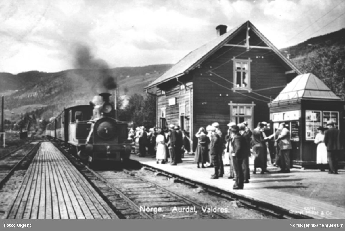 Et persontog ankommer Aurdal stasjon, med mange reisende på plattformen