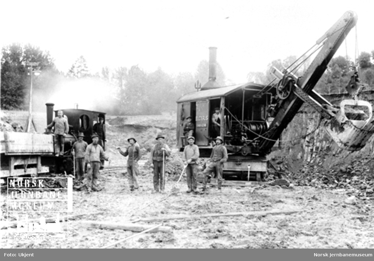 Anleggsdamplokomotiv med vagger og dampgravemaskin på verkstedtomten på Marienborg