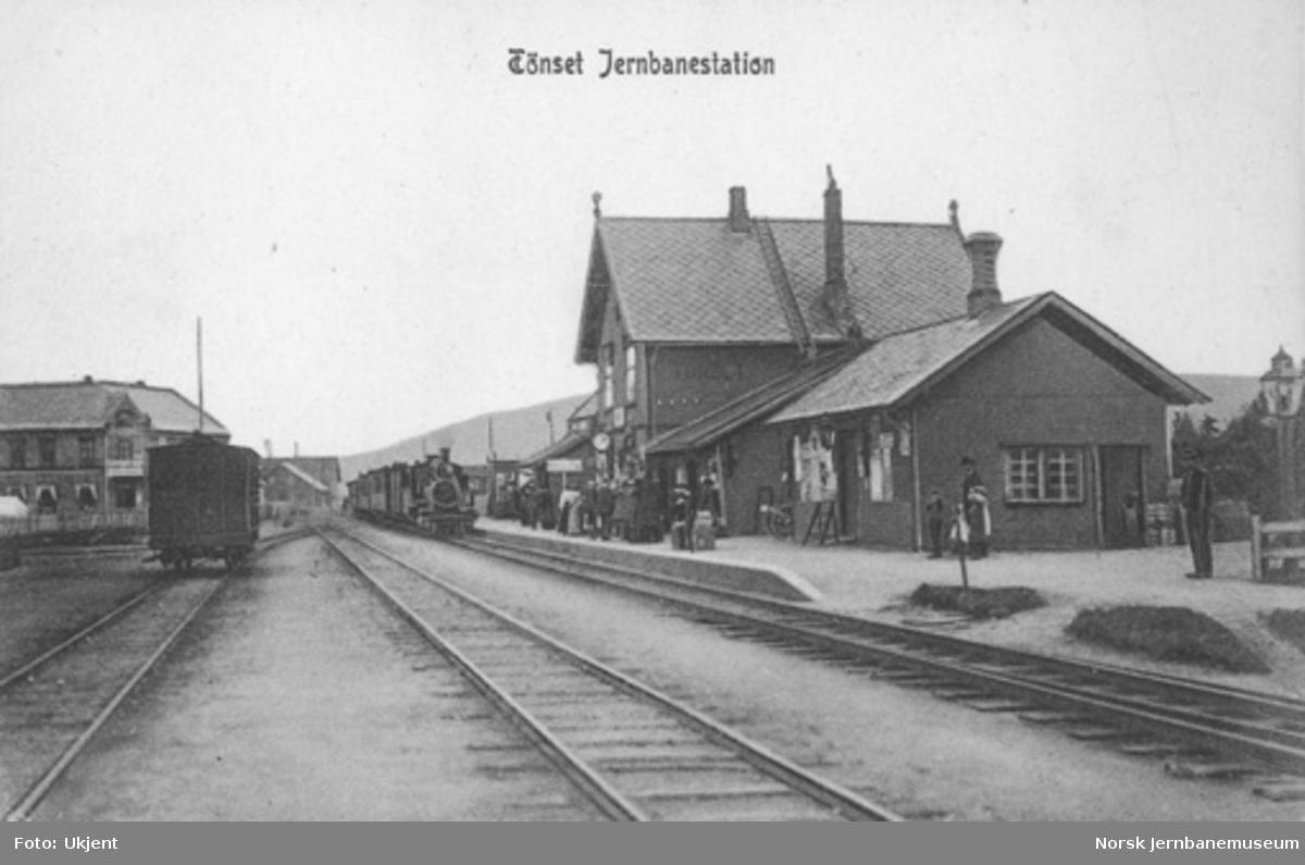 Tynset stasjon med ankommende tog i spor 1 og mange reisende