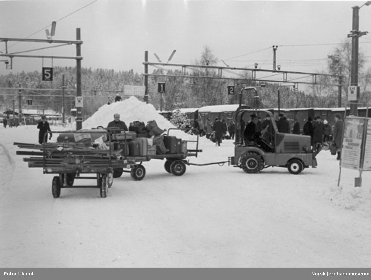 Plattformtraktor med reisegodstraller på Hønefoss stasjon : reisende i bakgrunnen