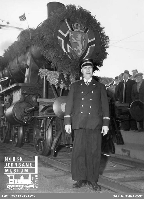 Vestfoldbanens åpningstog på normalspor : NSB-ansatt, trolig lokomotivfører Olaf Hansen, poserer foran lokomotivet