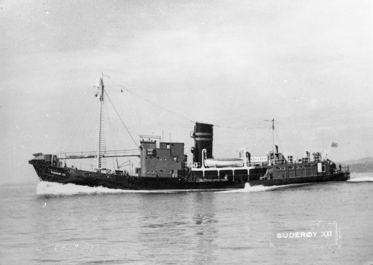 """Hvalbåten FL/K """"Suderøy"""" i åpent farvann.  Deler av mannskapet på baug og akter. Land i bakgrunnen til høyre."""