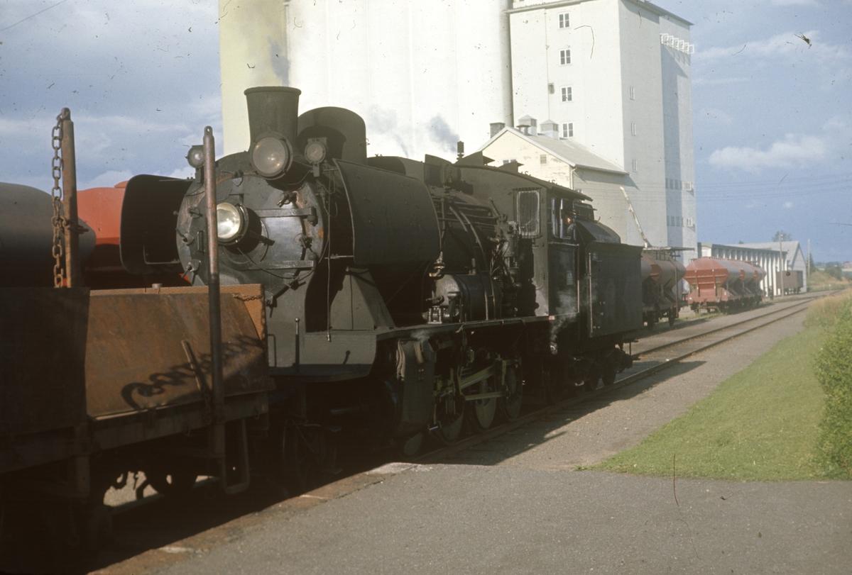 Godstog med damplok 24b 264 på Lena stasjon. Kornsiloen i bakgrunnen