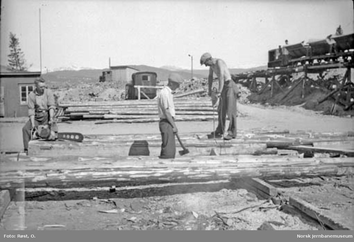 Kapping og boring av tømmer til snøoverbygg på jernbaneanleggets lagertomt på Langneset i Mo i Rana; anleggslokomotiver i bakgrunnen. Jernverkbanens transportspor til høyre.