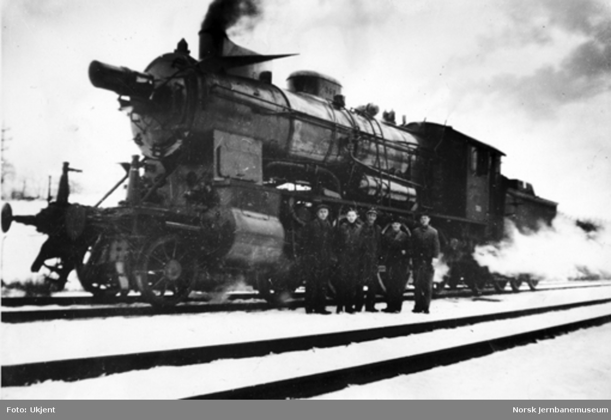 NSB damplokomotiv type 30b nr. 360 med blendet frontlyskaster og oppstilt personale