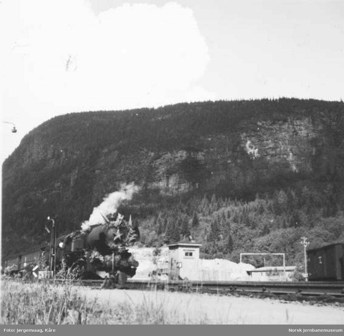 """Et dekorert damplokomotiv type """"stortysker"""" foran tog på Grong"""