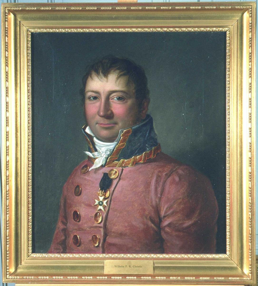 Portrett av sorenskriver Wilhelm F.K. Christie. Rød sorenskriveruniform, høy krave med gull, hvitt kalvekryss.  1 ordensstjerne.