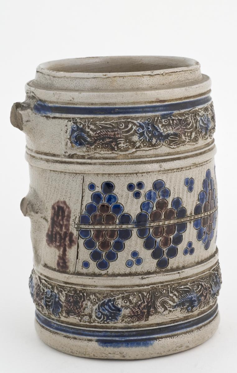 """Krus i grå keramikk av en type som stammer fra Westerwald-området i Tyskland. Karakteristisk er risset og stemplet dekor og pålagte relieffer, farget med koboltblått og senere også manganfiolett, under klar saltglasur. Dette lave, sylinderformete kruset kalles """"Humpen"""" og ble masseprodusert gjennom hele 1600 og 1700-tallet. Lokk i metall mangler. Hanken mangler."""