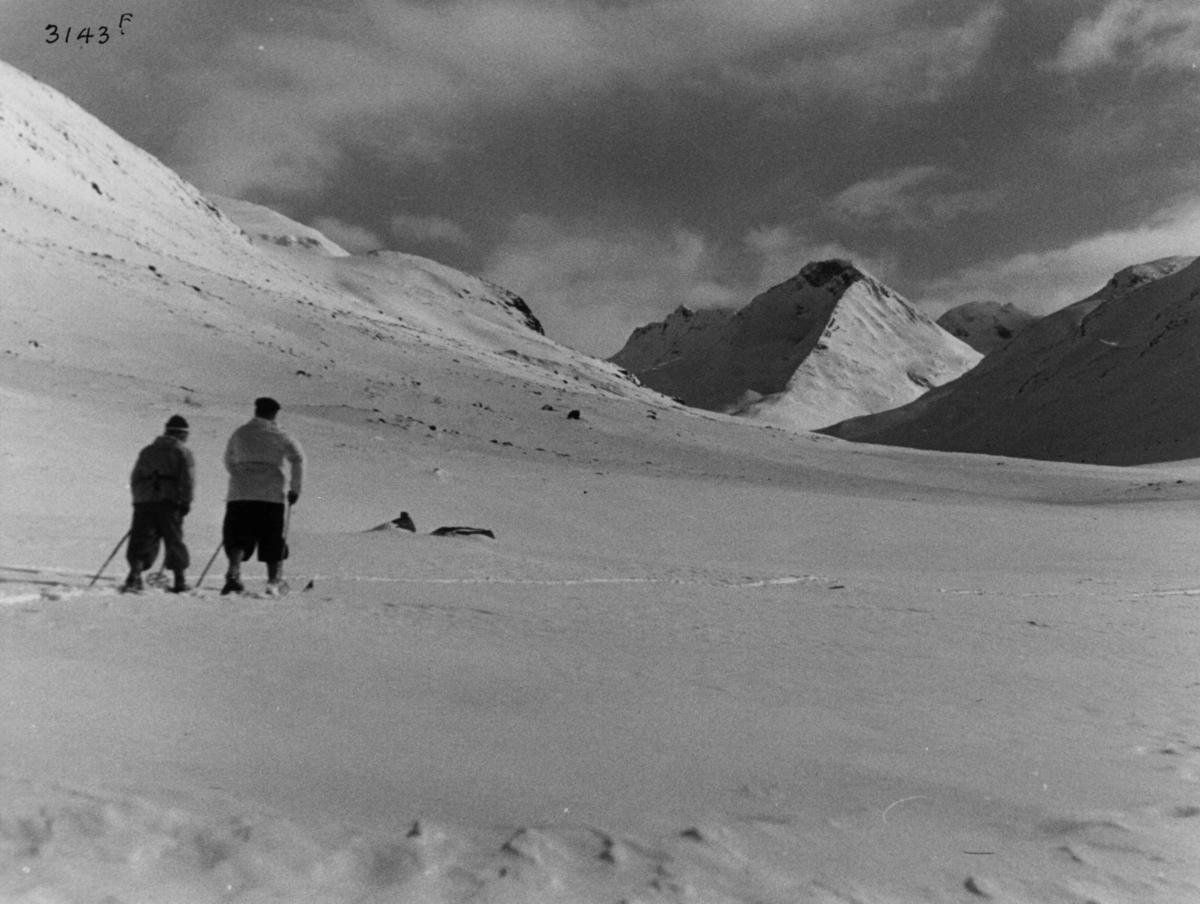 Skiløpere i Uladalen i Jotunheimen med snødekte fjell og sol.