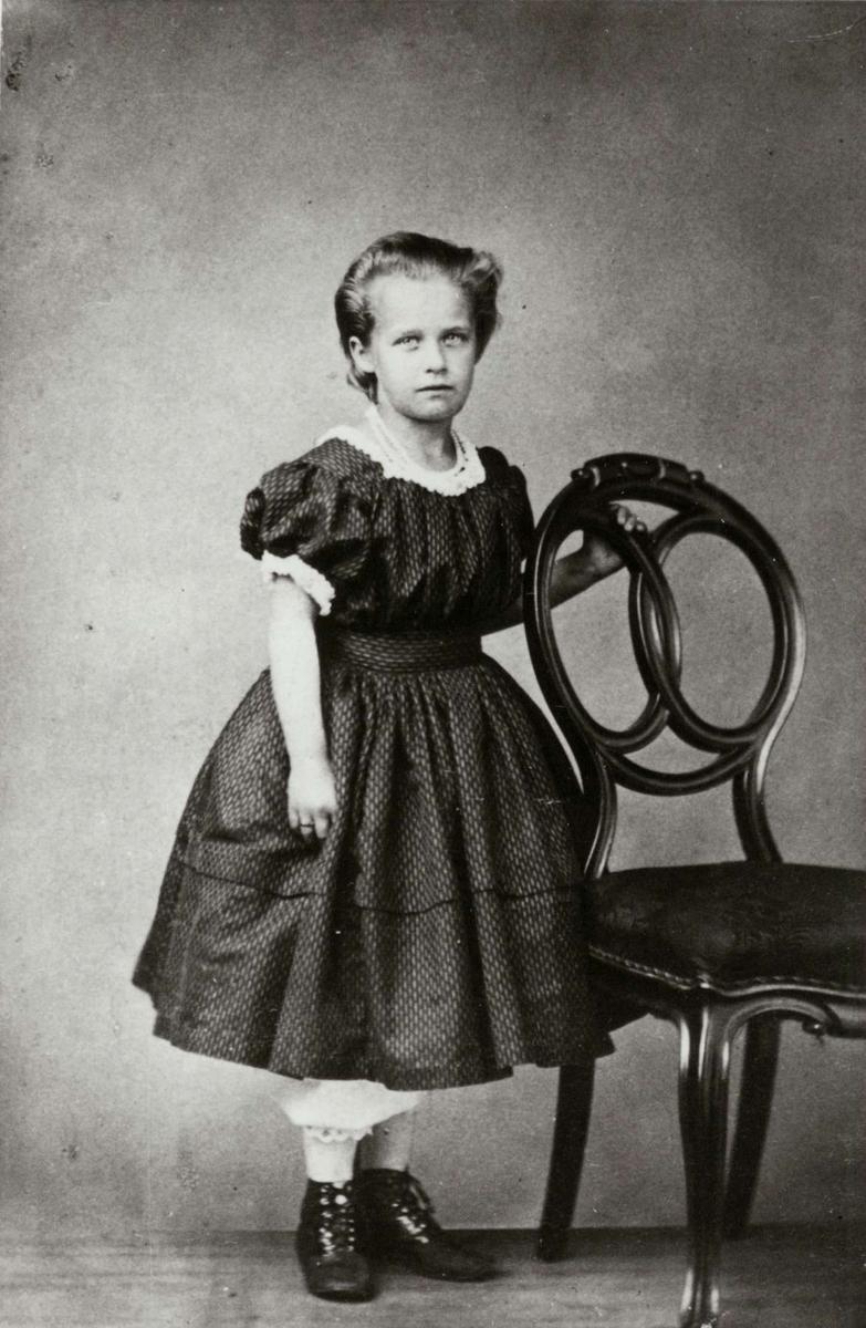 Portrett, Sofie Dahl, senere gift Gran, sorenskriver Dahls datter. Pike i kjole poserer ved stol i atelier. Hun er født ca. 1850.