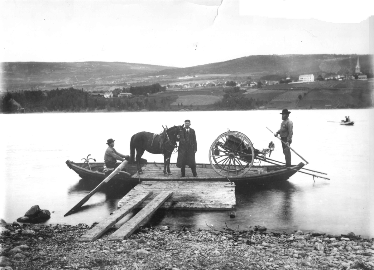 Fergetrafikk, robåt med to fergemenn frakter hest og kjøretøy over et vann. Personen ved hesten er muligens fotograf Marthinius Skøien selv. Bildet kan være av Lillehammer, tatt fra Vingnes.