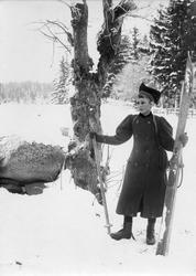 Kvinne med skipar i vinterlandskap, ukjent sted. Serie tatt av Robert Collett (1842-1913), amatørfotograf og professor i zoologi.