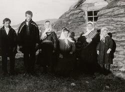 Familiegruppe (6) i samisk drakt, oppstilt foran gamme, Laks