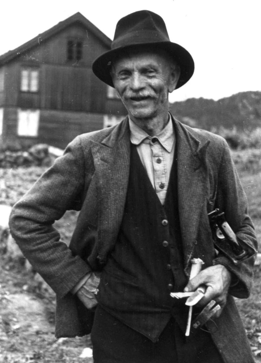 Portrett av Sigmund Rudlende med verktøy i den ene hånden. En bolig i bakgrunnen. Eiken 1941.