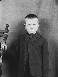 Portrett av gutt ved stol, Digerud, Frogn, Akershus, 1907. I