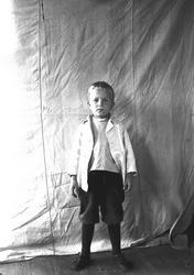 Portrett av gutt, fotografert mot opphengt bakteppe, ukjent