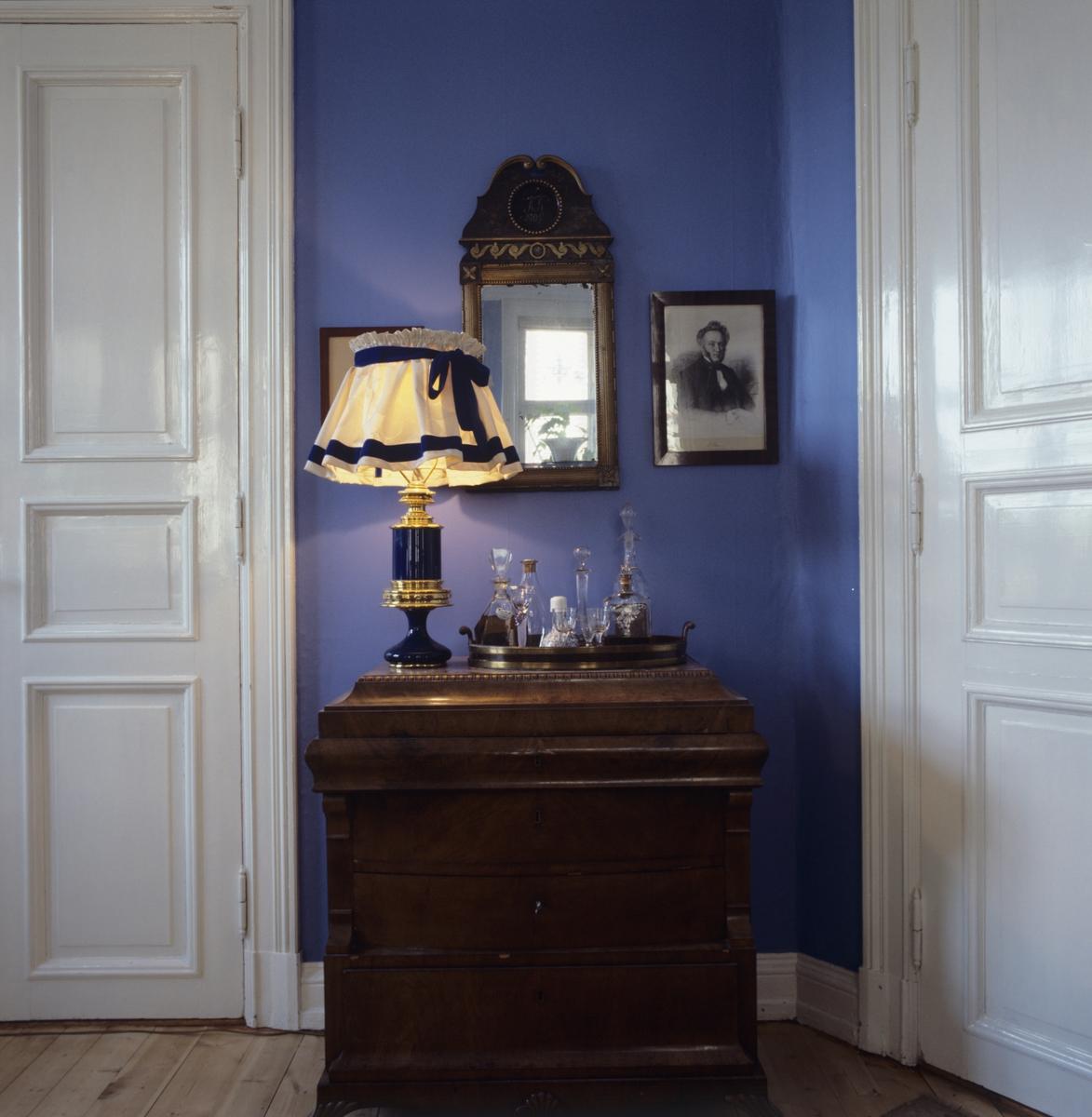 Kommode med  lampe og  brett med karafler . speil på veggen. llustrasjonsbilde fra Bonytt 1986.