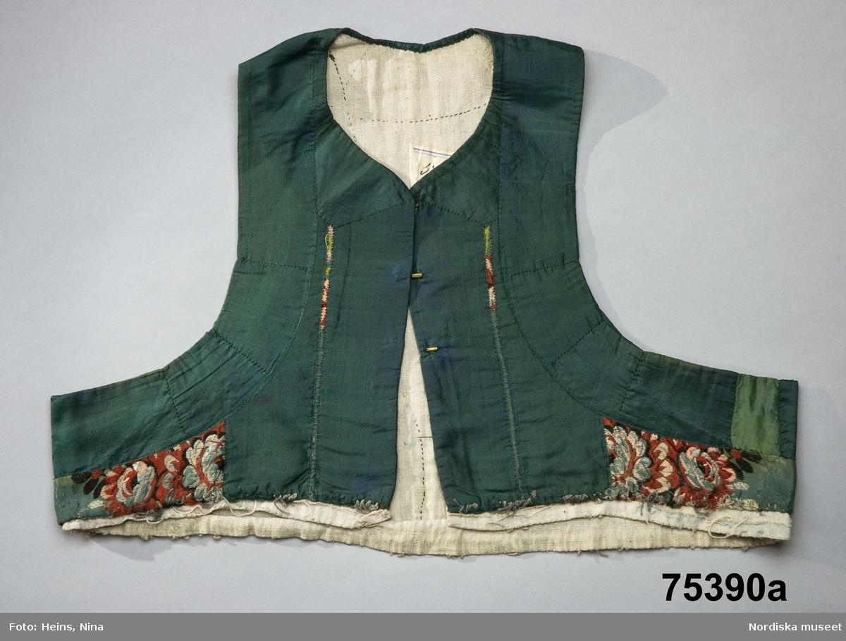 2 listycken a och b.  som suttit ihop med kjolar.  a.. Av sidenbrokad, grön botten, blommönster i silke i grönt,rött, rosa, ljusblått och vitt. Kantat med 5 cm breda gröna sidenband, i framkant i dubbla rader och i ryggen i två vinklar.Små insyningar på bandet för att passa ringningarna. Foder av  oblekt linnelärft. Nederkanten ofållad, sydd med kaststygn, trådrester av oblekt lingarn efter den bortsprättade kjolen. I framkanterna  3 par hakar och hyskor av fabriksgjord typ.  b .Av något äldre typ av sidenbrokad, ljusblå med sirligare blommönster i rosa, vitt och grönt. 3 cm smala gröna sidenband, i enkla rader i framkant med märken efter 3 par maljor. Foder av linnelärft. Nederkanten som a. /Berit Eldvik 2008-04-08
