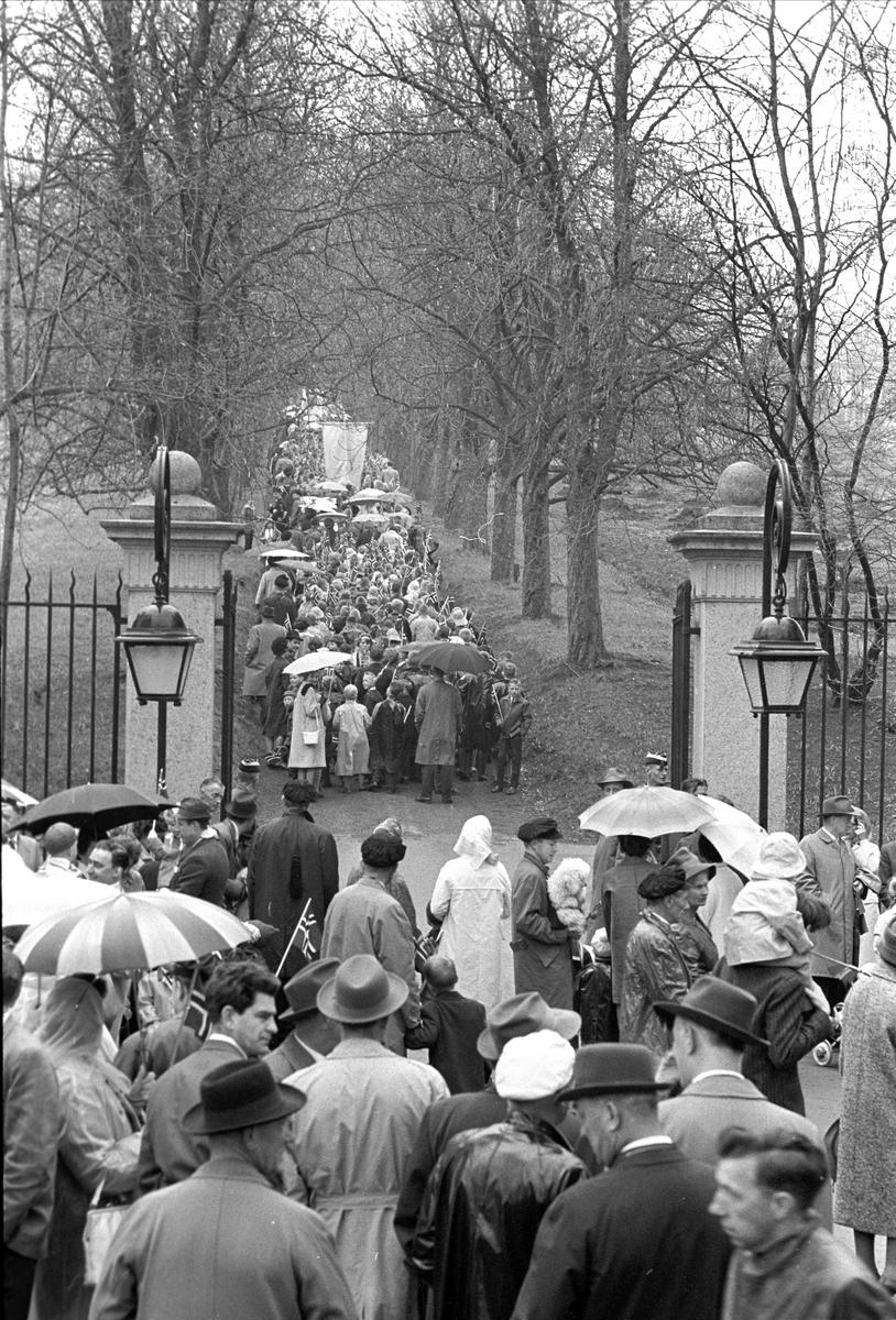 Fra Oslo,17.05.1963. Sammenstimling av folk foran en port for å se toget forsvinne opp en allé på 17. mai i regnværet.